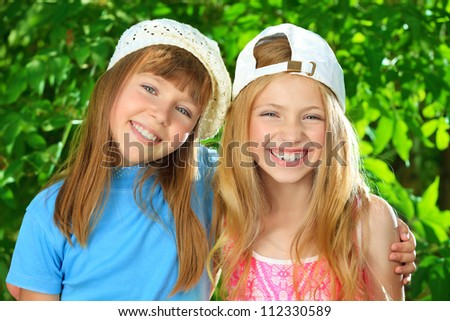 Two cheerful girls at the summer park. - stock photo