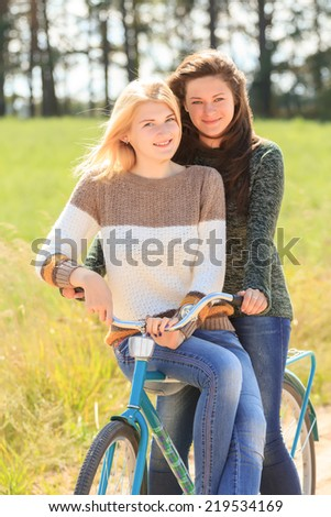 Two cheerful girls during cycling on dirt road - stock photo