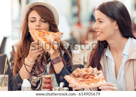Two cheerful  girls eating pizza in a outdoor cafe.