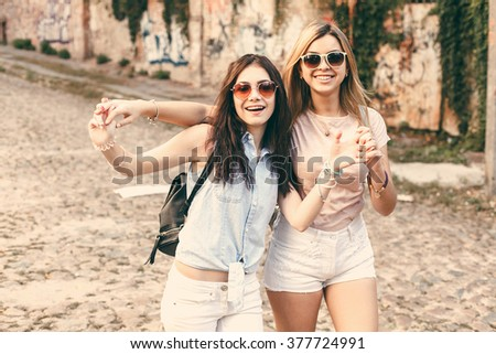 Two cheerful girls in a city walk and laugh. Pastel colors - stock photo