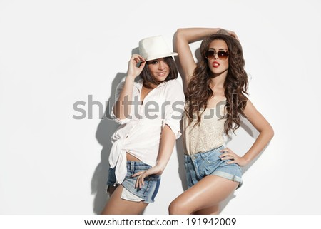 two cheerful girls in casual clothes - stock photo