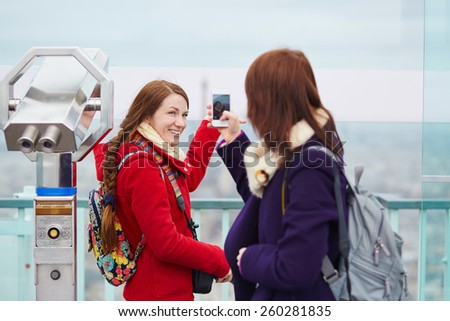 Two cheerful girls in Paris, making pictures of each other on the observation deck of the Montparnasse tower with mobile phone - stock photo