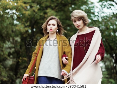 Two cheerful girls  in the autumn park - stock photo