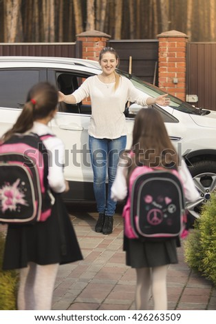Two cheerful girls running to mother meeting them after school - stock photo