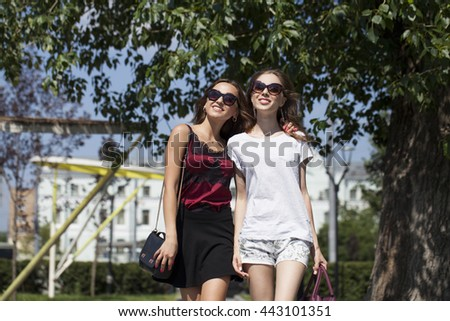 Two cheerful girls, summer street outdoors - stock photo