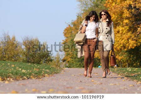 Two cheerful girls twins, in the autumn park - stock photo