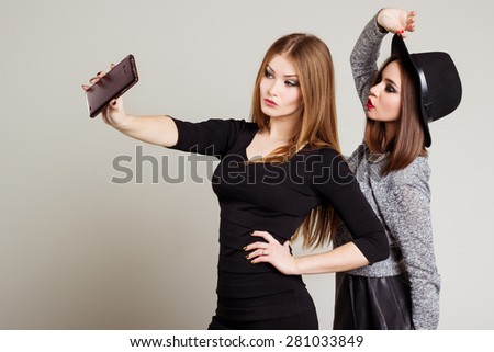 Two cheerful happy girl girlfriends photographed on the phone, Self phone - stock photo