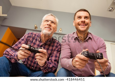 Two cheerful happy men playing video games with joysticks - stock photo