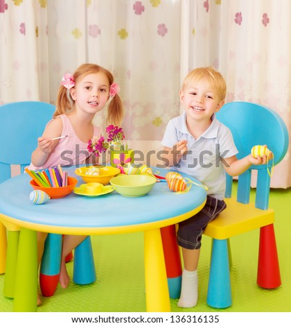Two cheerful kids paint Easter eggs at home, handmade festive decorations, spring holiday, happiness concept - stock photo
