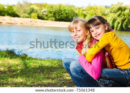 Two cheerful  little girls embracing - stock photo