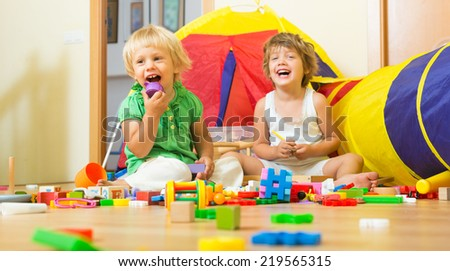 Two cheerful little girls playing with blocks in home interior  - stock photo