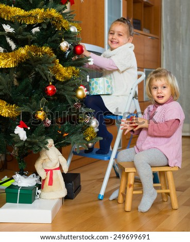 Two cheerful little sisters decorating Christmas decorations on New Year tree at home