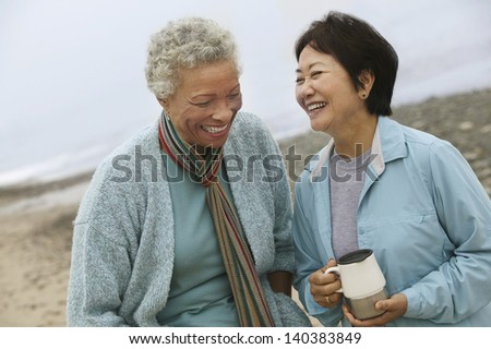 Two cheerful middle aged female friends talking on the beach - stock photo