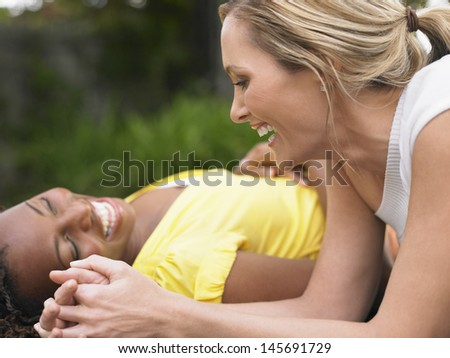 Two cheerful multiethnic women lying outdoors and laughing - stock photo