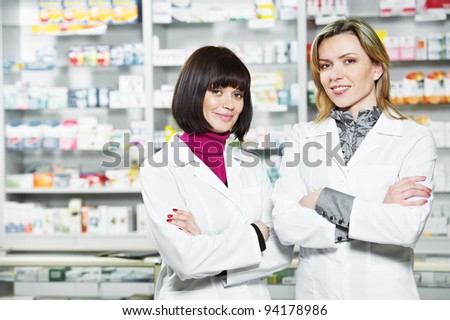 Two cheerful pharmacist chemist woman standing in pharmacy drugstore - stock photo