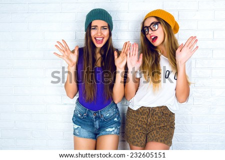 Two cheerful pretty hipster girl wearing mini swag denim shorts bright hats and glasses put their hands to the air smiling and having fun. - stock photo