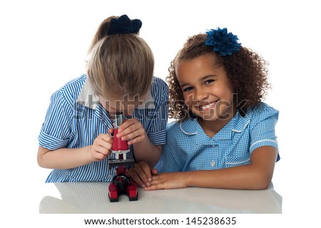Two cheerful school kids with a microscope - stock photo