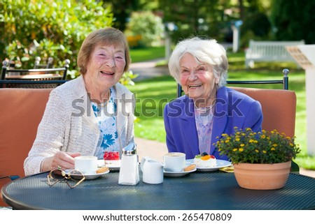 Two Cheerful Senior Female Best Friends Sitting at the Outdoor Table with Coffee and Snacks. - stock photo