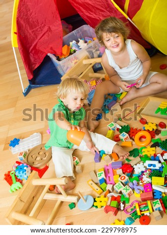 Two cheerful siblings playing with toys together at home - stock photo