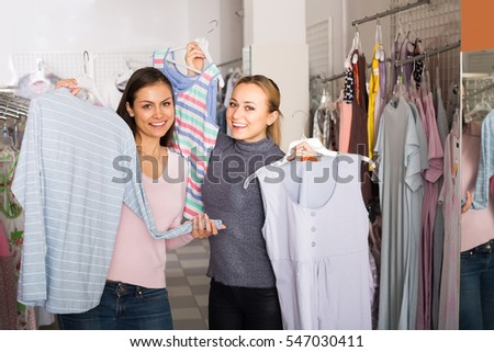 Two cheerful smiling  female friends selecting comfortable sleepwear together in lingerie department