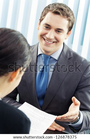 Two cheerful smiling young businesspeople, or business man and client, working with document at office - stock photo