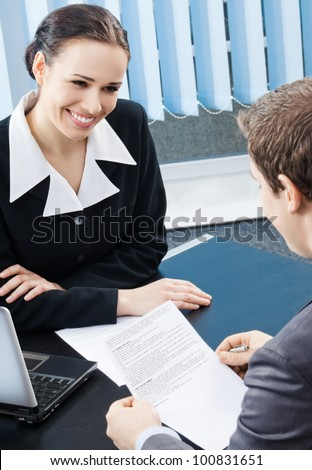 Two cheerful smiling young businesspeople, or business woman and client, working with document at office - stock photo