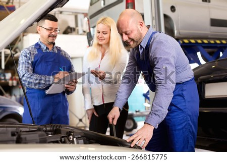 Two cheerful troubleshooters showing fixed car to client - stock photo