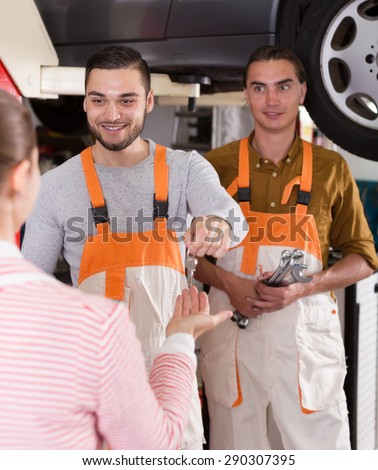Two cheerful troubleshooters showing fixed car to satisfied client - stock photo