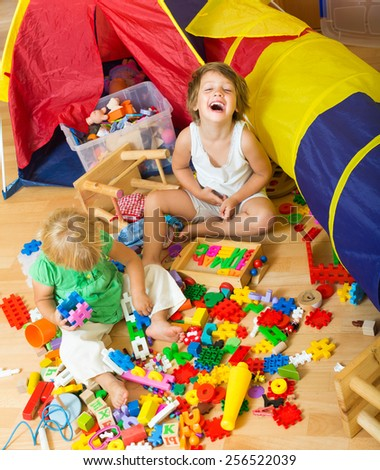Two cheerful �ute little sisters playing with toys together in home interior