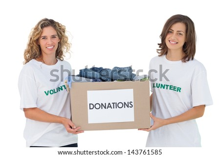 Two cheerful volunteers carrying clothes donation box on white background - stock photo