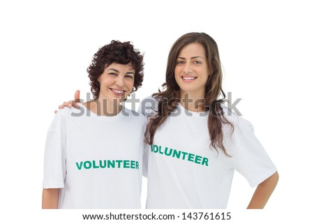 Two cheerful volunteers standing on white background - stock photo