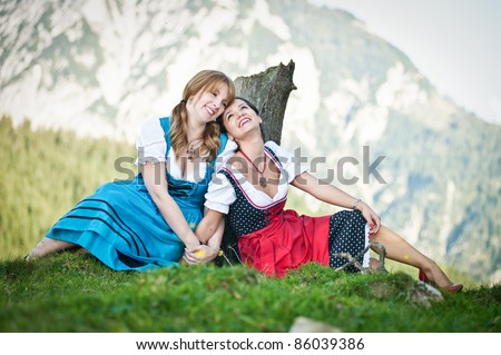 Two cheerful woman dressed in dirndl in the austrian alps
