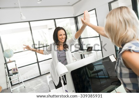 Two cheerful women in office giving high five - stock photo