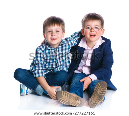 Two cheerful young boys are sittiing together. Isolated on the white background - stock photo
