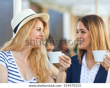 Two cheerful young girlfriends sitting in a cafe drinking coffee - stock photo