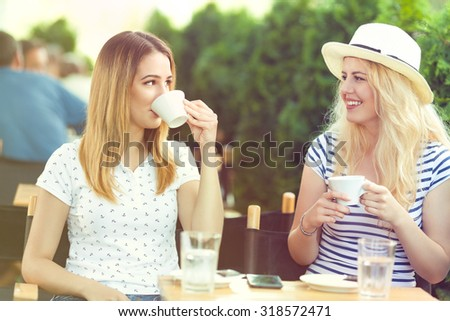 Two cheerful young girlfriends sitting in a sidewalk cafe drinking coffee enjoying nice sunny day - stock photo
