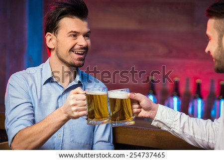 Two cheerful young men in shirt with beer while sitting together at the bar counter. - stock photo