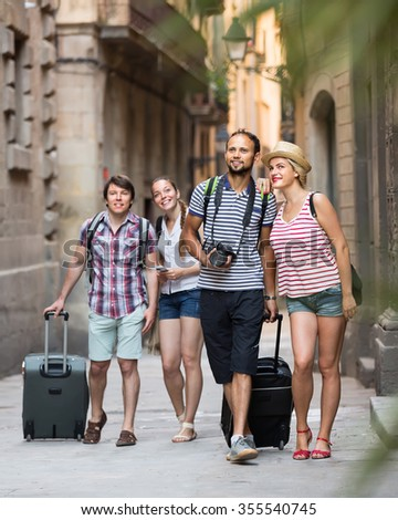 Two cheerful young tourist couples with travel bags walking through european city. Selective focus - stock photo