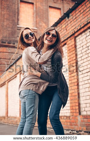 Two cheerful young woman against a brick wall. Best friends - stock photo