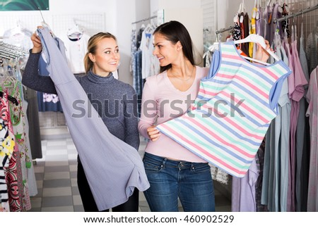 Two cheerful young women together choosing pajamas in lingerie store