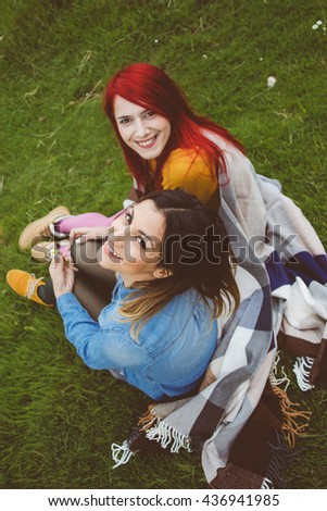 Two cheering attractive young women sitting in the vivid meadow - stock photo