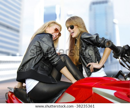 two cheery beautiful blonde motorcyclists and red motorcycle - stock photo