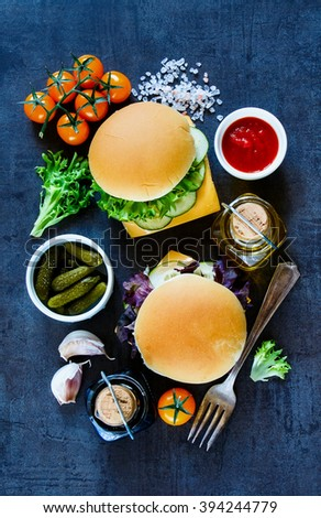 Two cheese sandwiches with fresh vegetables on dark vintage background, border, top view. Vegetarian and healthy eating concept. - stock photo