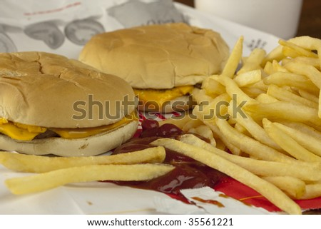 Two cheeseburgers and french fries on a fast food bag - stock photo