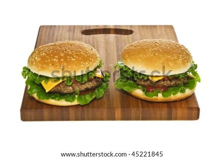 Two cheeseburgers on wooden cutting board isolated on white.
