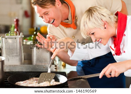 Two chefs in teamwork - man and woman - in a restaurant or hotel kitchen cooking delicious fish in pan - stock photo