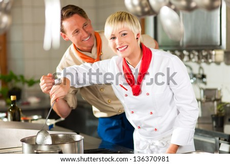 Two chefs in teamwork - man and woman - in a restaurant or hotel kitchen cooking delicious food - stock photo
