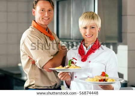 Two chefs in teamwork - man and woman - in a restaurant or hotel kitchen cooking delicious food, both are presenting the finished dishes - stock photo