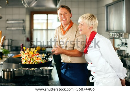 Two chefs in teamwork - man and woman - in a restaurant or hotel kitchen cooking delicious food, he is working on the ratatoulle in the pan - stock photo