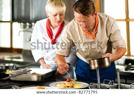 Two chefs in teamwork - man and woman - in a restaurant or hotel kitchen cooking delicious food, he is decorating the dishes, she is watching